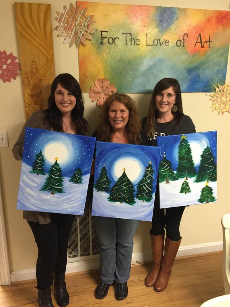 Adult daughters and me holding our Christmas tree artwork