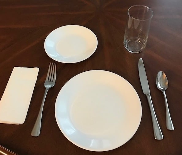 Family dinner place setting with plates, fork, knife, spoon, and napkin