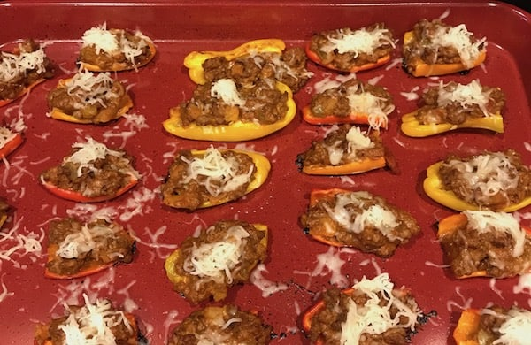 Cooked mini stuffed peppers sprinkled with shredded mozzarella cheese