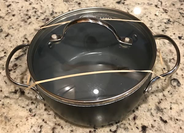 Rubber band stretched over the lid of a pot and looped around the handles on either side.