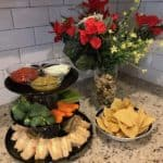 Party platter with sandwiches, chips, and dip, and a bowl of chips