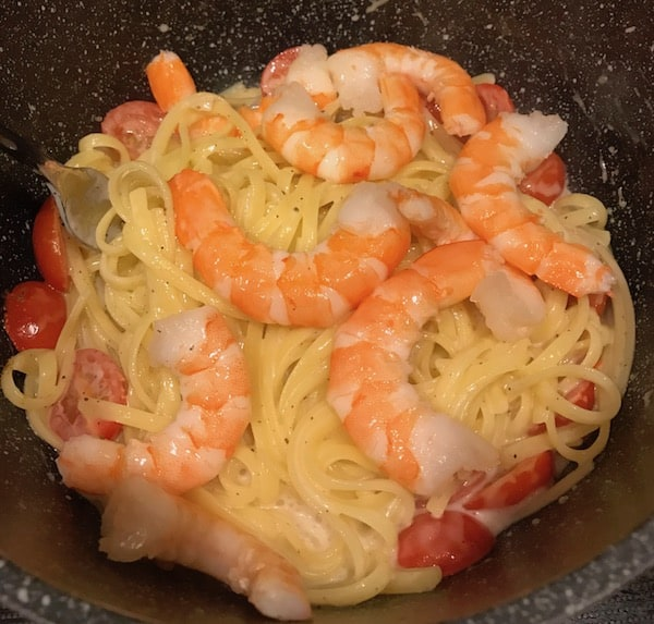 Shrimp, tomatoes, and dressing in cooked fettuccine