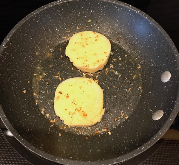 Slices of polenta sprinkled with a seasoning blend in the frying pan