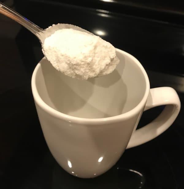 Spoon of cake mix over a coffee mug