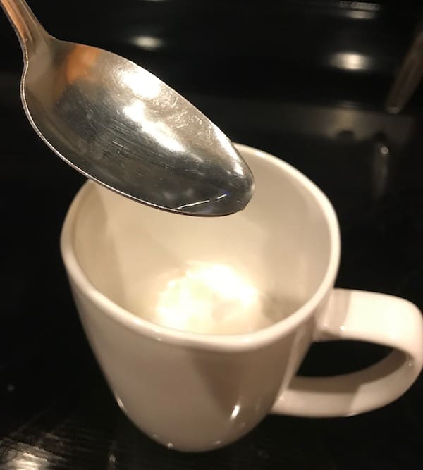 Spoon of water over mug of cake mix
