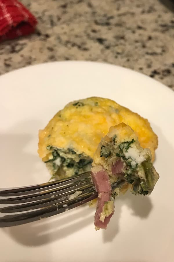 Bite of egg muffin cup with fork in ham.