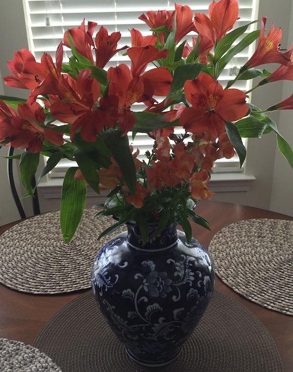 Southern mamas love floral centerpieces. Here is a bouquet of coral alstroemeria in a blue and white vase in the center of a table.