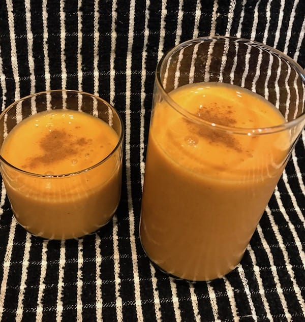 Two pumpkin pie smoothies with cinnamon sprinkled on top