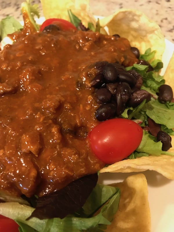 Scoop a layer of chili over the Mexican salad.