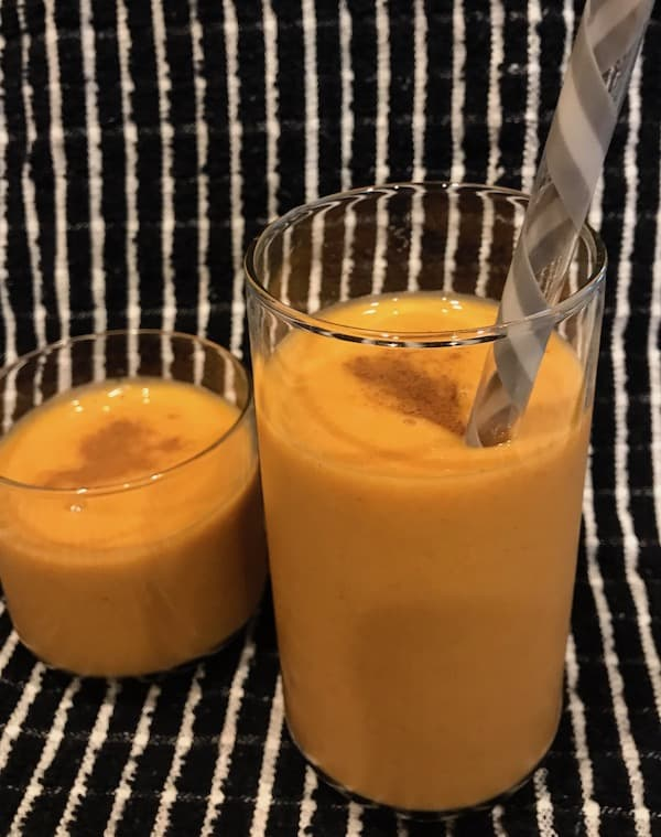 Two pumpkin smoothies sprinkled with cinnamon, one with a large straw