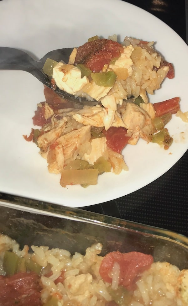 Transferring a spoonful of chicken creole from the casserole dish to the plate.