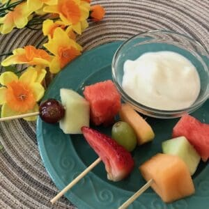 3 fruit kabobs with a small bowl of vanilla yogurt