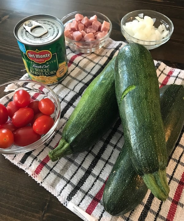 Corn, tomatoes, ham, onions, and zucchini are all used to make this zucchini bake.