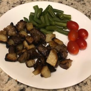 Plate of beef hash, green beans, and tomatoes