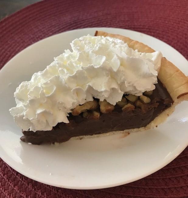 Slice of chocolate walnut pie with whipped cream
