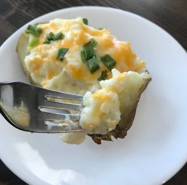 Taking a bite of a twice baked potato.