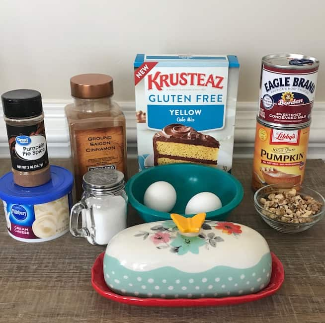 cake mix, sweetened condensed milk, can of pumpkin, crushed walnuts, eggs, cream cheese frosting, pumpkin pie spice, cinnamon, butter, and salt