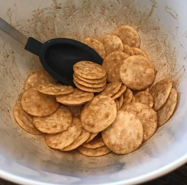 Stirring the seasoning mix to coat the crackers.
