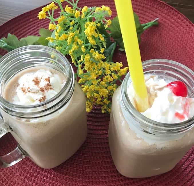 2 mugs of coffee smoothie--1 with whipped cream and cinnamon and 1 with whipped cream and a cherry