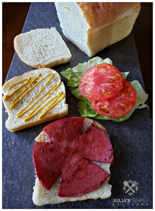 Fried bologna sandwich with mustard, tomatoes, lettuce, and bread - school lunchbox ideas
