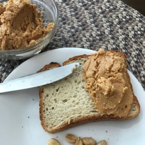 Peanut butter on bread next to a bowl of peanut butter