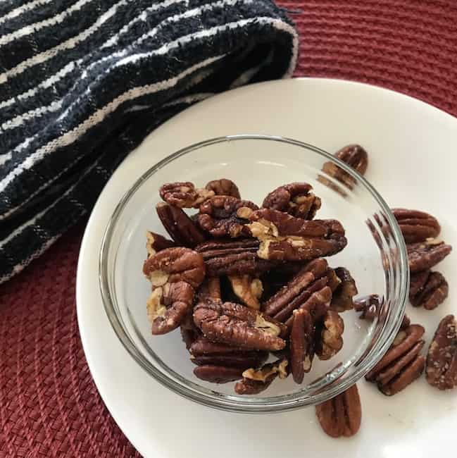 Pecans in a glass bowl and on a plate